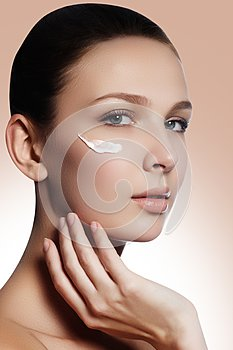 Beautiful face of young woman with cosmetic cream on a cheek. Sk