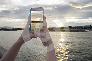 Close up of woman's hand holding smart phone, mobile, smart phone over blurred beautiful sea with sunset moment to take a pho