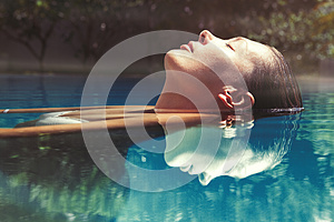 Enjoy the summer. Woman relaxing in the pool water
