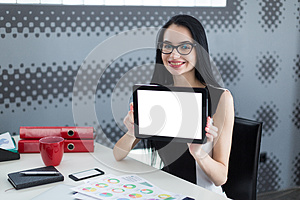 Young student woman in office holding a tablet and smiling