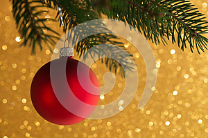 Red decorative ball on the xmas tree on glitter bokeh background. Merry christmas card.