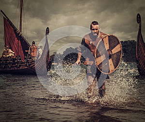 Viking warrior in the attack, running along the shore with Drakkar on the background.
