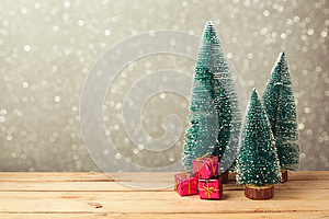 Christmas gift boxes under pine tree on wooden table over bokeh background