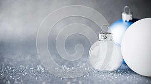 Blue, silver and white xmas ornaments on glitter holiday background. Merry christmas card.