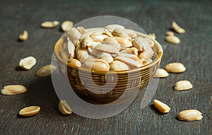 Roasted peeled salted peanuts in rustic bowl on wooden background