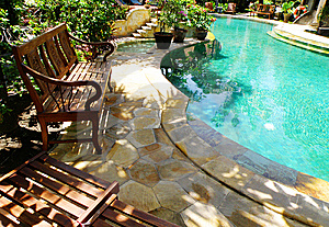 Sunny outdoor swimming pool and patio furniture