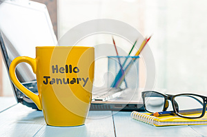 Hello January written on yellow coffee cup at manager or freelancer workplace. New year time concept. Business and