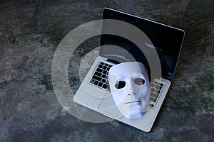Anonymous mask to hide identity on computer laptop - internet criminal and cyber security threat concept