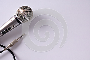 Wired microphone with connector on white table closeup top view