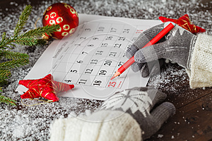 Gils in glowes mark calendar with christmas date