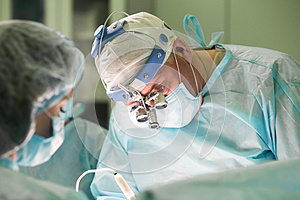 Surgical team during performing cosmetic surgery in hospital ope