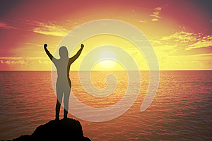 Silhouette of winning success woman at sunset or sunrise standing and raising up hand in celebration of having reached mountain.