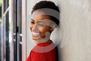 Smiling young black woman leaning against wall outside