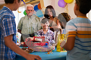 Boy With Family And Friends Celebrating Birthday Party