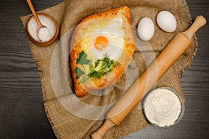 Khachapuri with eggs on sackcloth, flour, eggs and salt on black table
