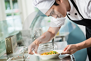 Gourmet chef plating up a dish of food