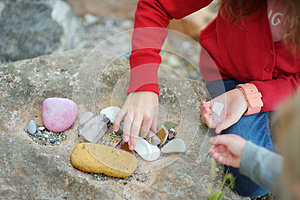 Two cute little sisters collecting beautiful stones on a pebble beach