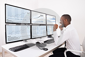 Happy Stock Market Broker Looking At Graphs On Multiple Computer