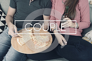 Young couple eating pizza with sign