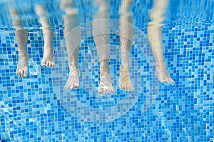 Funny underwater family legs in swimming pool, under water view of mother and kids, vacation fitness