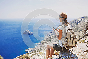 Hiking woman using smart phone taking photo, travel and active lifestyle concept