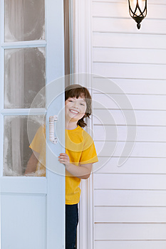 Child opens the door of a house