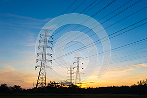 Silhouette high voltage electricity pylon on sunrise background