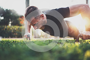 Muscular athlete exercising push up outside in sunny park. Fit shirtless male fitness model in crossfit exercise