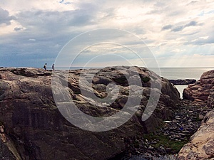 two undefined people walking on a rock by the sea in Sweden