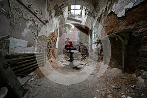 Red barber chair in a jail cell