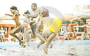Multiracial friends having fun jumping at swimming pool party aquapark