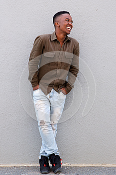 Full body happy black man leaning against gray wall