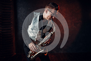 Male saxophonist playing jazz melody on saxophone