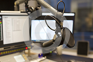 Studio microphone in front of radio station broadcasting equipment