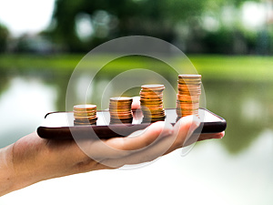 Close up stack of money coins on the mobile phone, business in eCommerce concept
