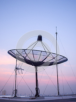 Portrait view of satellite dish on top of the building.