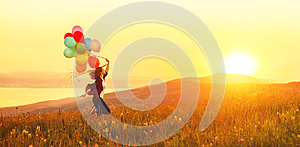 Happy cheerful girl with balloons running across meadow at sunset in summer