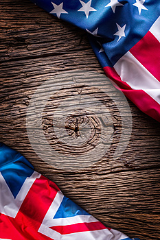 Flags of american and united kingdom on rustic oak board. UK and USA flags together diagonally