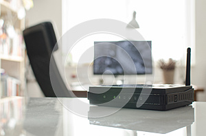 Black wireless router on white reflective table