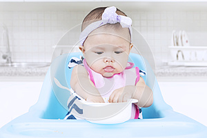 Sweet baby eating with bowl on chair