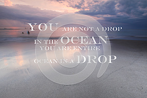 Blurry sunset on the beach with Inspirational quote You are not a drop in the ocean you are entire ocean in a drop