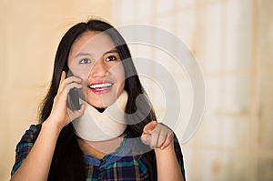 Headshot young hispanic woman posing wearing neck brace, smiling happily while talking on phone, injury concept
