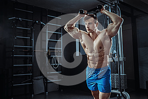 Sexy muscular man posing in gym, shaped abdominal. Strong male naked torso abs, working out