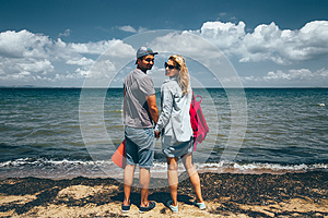 Couple Travelers Man And Woman Standing On Seashore And Looks At The Camera Adventure Travel Journey Concept