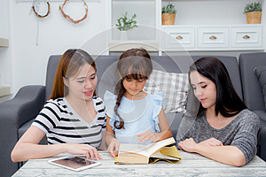 happy family mother, aunt, freind and daughter teaching read a book.