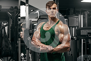 Muscular man showing muscles working out in gym, strong male with big biceps