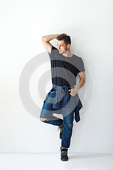 Full length portrait of handsome stylish man leaning at white wa