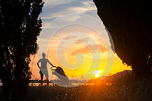 Silhouette of mother with stroller enjoying motherhood at sunset