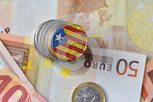 Euro coin with national flag of catalonia on the euro money banknotes background