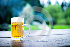 Glass of light beer with foam on a wooden table. Garden party. Natural background. Alcohol. Draft beer.